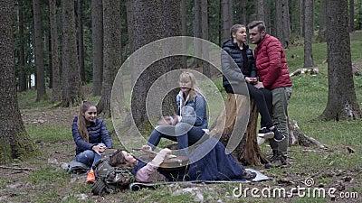 Счастливая группа в составе друзья располагаясь лагерем в древесинах наслаждаясь природой играя гитару и поя совместно лежать вни видеоматериал