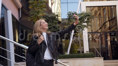 Счастливая девушка делая фото selfie на камере прибора смартфона и представляя около современной строя предпосылки outdoors видеоматериал