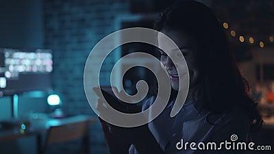 Счастливая девушка используя содержание смартфона наблюдая на экране в темном офисе вечером акции видеоматериалы