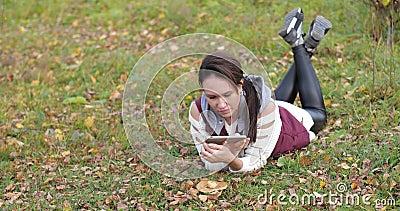 Счастливая девушка лежа в парке на траве Фото на телефоне Желтое листво акции видеоматериалы