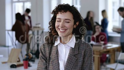 Счастливая европейская молодая бизнес-леди усмехаясь жизнерадостно в элегантном официальном костюме с вьющиеся волосы, представля видеоматериал