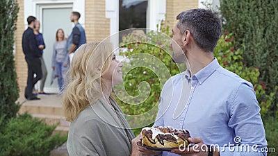 Счастливая зрелая пара с улыбкой торта и взглядом на камеру, стоящую на переднем плане, в то время как компания людей разговарива акции видеоматериалы