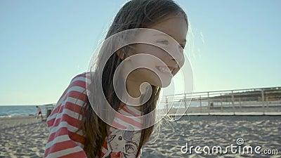 Счастливая малая девушка стоит, бежит, и падает на пляж моря, на заход солнца в slo-mo видеоматериал