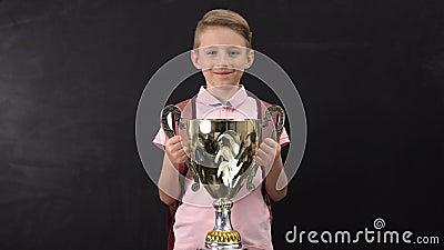 Счастливая награда шара удерживания школьника, выигрывая турнир спорт, успешный ребенок сток-видео