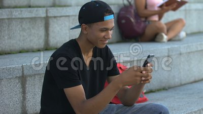 Счастливого афро-американского подростка, общавшегося по смартфону на ступенях кампуса, нового приложения акции видеоматериалы