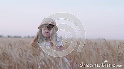 Счастливое детство деревни, меньшая милая девушка с соломенной шляпой имея потеху и смеясь закрутками в собраных шипах пшеницы зе акции видеоматериалы