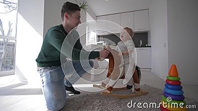 Счастливое детство, молодой папа играя со славным младенческим мальчиком на посадочных местах плюша equine и отбрасывая дома в ку акции видеоматериалы
