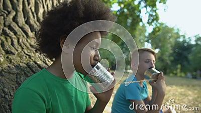 Счастливые многонациональные друзья, говорящие через банки, счастливое детство без гаджетов сток-видео