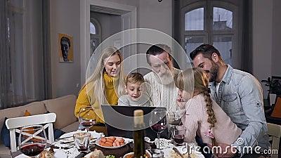 Счастливые радостные семьи смотрят красивые фотографии на компьютере, показывающие, как они уважают старшего дедушку, сидя вместе сток-видео