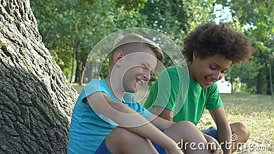 Счастливые школьники, сидящие под деревом в парке, веселятся вместе, детство акции видеоматериалы
