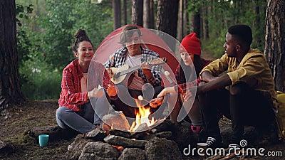 Счастливые hikers варят зефир на огне и песни петь пока красивый парень играет гитару во время убежища акции видеоматериалы