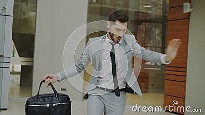 Счастливый и смешной бизнесмен с танцами портфеля в лобби офиса пока никто наблюдая его