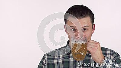 Счастливый молодой человек смотря возбужденное, выпитое очень вкусное пиво, усмехаясь счастливо акции видеоматериалы