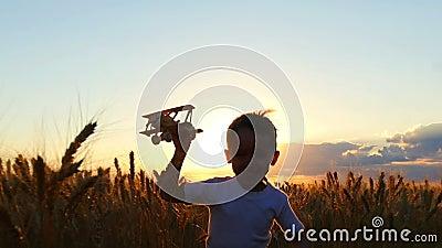 Счастливый ребенок бежит через пшеничное поле во время захода солнца, держа самолет игрушки Мальчик показывает полет