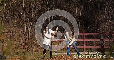 2 счастливых девушки очищают листья в парке Желтое листво видеоматериал