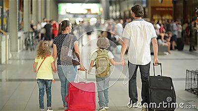 Счастливая семья при маленькая девочка и мальчик идя на железнодорожный вокзал, отец матери и дети идут через авиапорт с сток-видео