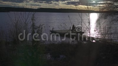 Съемка слайдера посадочных мест девушки на стенде на деревянной палубе озером во время времени захода солнца видеоматериал