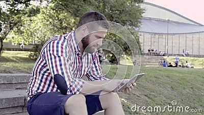 Таблетка просматривать молодого человека, сидя на лестницах съемка слайдера акции видеоматериалы