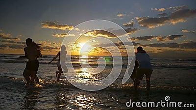 Танцы группы людей скача и потеха иметь в воде на пляже на заходе солнца - замедленном движении видеоматериал