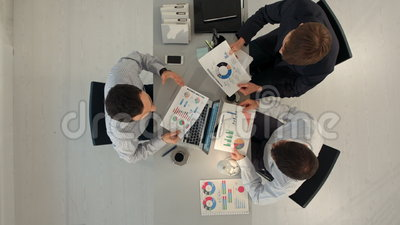 Творческая команда показывая диаграммы с компьтер-книжкой и акции видеоматериалы