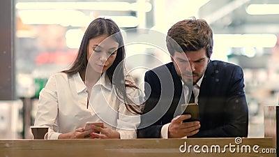 Технологии и концепция людей - бизнес-пара с смартфонами, пытающиеся использовать новые приложения на своих телефонах видеоматериал
