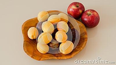 Тиковая тарелка заполнена сливами, абрикосами и яблоками сток-видео