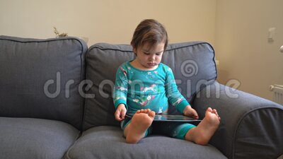 Тоддлер сидит на диване и играет в игры на планшете, смотрит мультфильмы современное детство видеоматериал