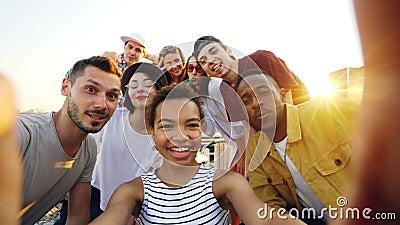 Точка зрения сняла Афро-американской девушки держа камеру и принимая selfie с счастливыми друзьями на партии на крыше Мужчины