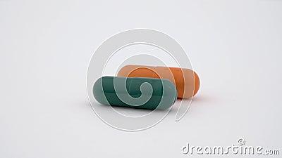 2 трудных капсулы крахмала вращая на таблице поворота Оранжевый и зеленый цвет белизна изолированная предпосылкой конец вверх сток-видео