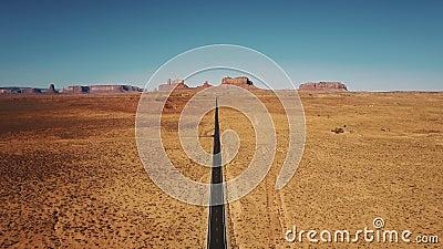 Трутень летая ОН назад высоко над пустой дорогой пустыни песчаника в долине памятников, Аризоне с плоским горизонтом гор видеоматериал