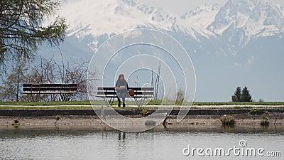 Туристка сидит на скамейке у горного озера, вынимает карту из рюкзака и начинает смотреть на карту видеоматериал