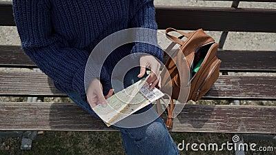 Туристка сидит на скамейке у горного озера, вынимает карту из коричневого рюкзака и начинает смотреть на карту Закрыть сток-видео