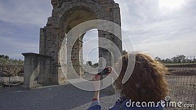 Туристка фотографирует с камерой Арку Капарры, древнего римского города Капарра в Эстремадуре, Испания акции видеоматериалы