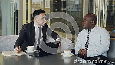 2 уверенно бизнесмена обсуждая о партнерстве во время встречи в современном стекловидном кафе акции видеоматериалы