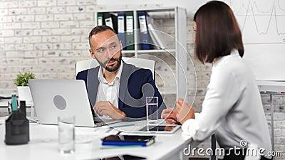 Уверенный бизнесмен разговаривает с работницами, обсуждая бизнес, смотря на экран ноутбука видеоматериал