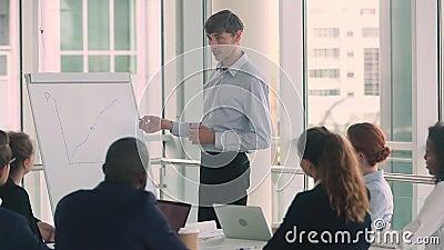 Уверенный серьезный мужской диктор тренера дела дает корпоративное представление flipchart видеоматериал