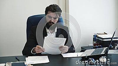 Уверенный человек бизнесмена смотря через бумаги и быть сердитый в офисе Усилие на работе акции видеоматериалы
