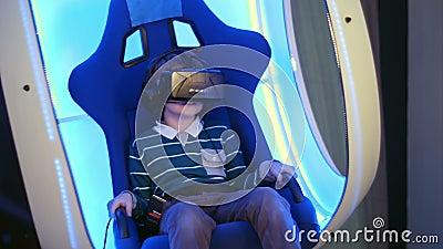 Удивленный мальчик, испытывающий виртуальную реальность в движущемся интерактивном кресле видеоматериал