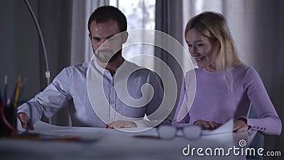 Удовлетворенная кавказская женщина показывает клиенту свой план Жирный клиент-мужчина изучает рисунки Профессиональный архитектор сток-видео