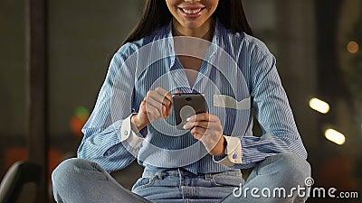 Удовлетворенный усмехаясь женский клиент перечисляя онлайн ходя по магазинам применение, банк акции видеоматериалы