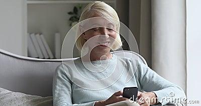 Улыбающаяся женщина средних лет наслаждается использованием смартфона сидя на диване сток-видео