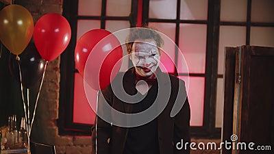 Улыбающийся страшный клоун в коричневой куртке с красным шаром акции видеоматериалы