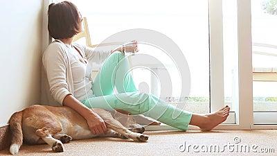 Унылая женщина распологая на пол около дружелюбной собаки сток-видео