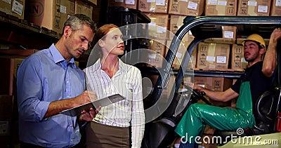 Управление склада разговаривая с водителем грузоподъемника позади акции видеоматериалы