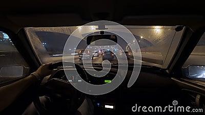 Упущение движения снятое мужского водителя сидит держащ руль в автомобиле, ехать в городе ночи акции видеоматериалы