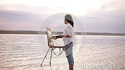 Ускоренная ход стрельба, художник девушки в воде до лодыжек рисует ландшафт используя мольберт и палитру курчавая девушка видеоматериал