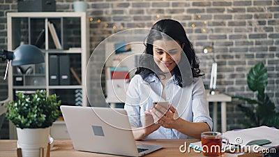 Усмехаясь девушка используя содержание смартфона наблюдая на экране в рабочем месте акции видеоматериалы
