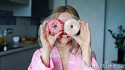 Усмехаясь девушка покрывая его глаза с застекленными donuts Милая женщина имея потеху сток-видео