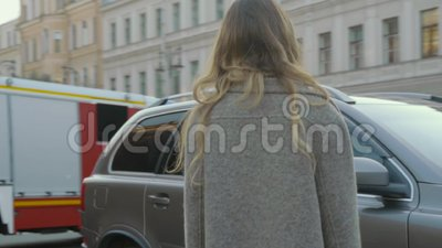Усмехаясь девушка развлекает на улице города с барочным зданием и автомобилях в slo-mo сток-видео