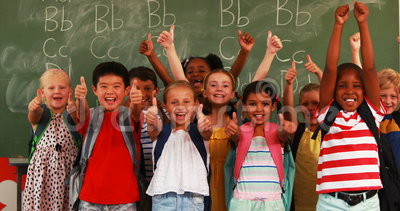 Усмехаясь дети показывая большие пальцы руки вверх в классе